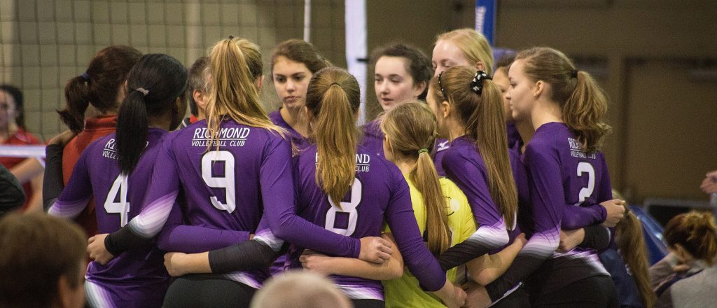 Girls team in purple uniforms team huddle before a game