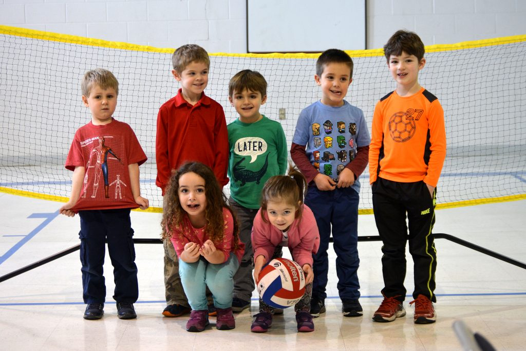 Group photo of preschoolers in front of a volleyball net at their preschool
