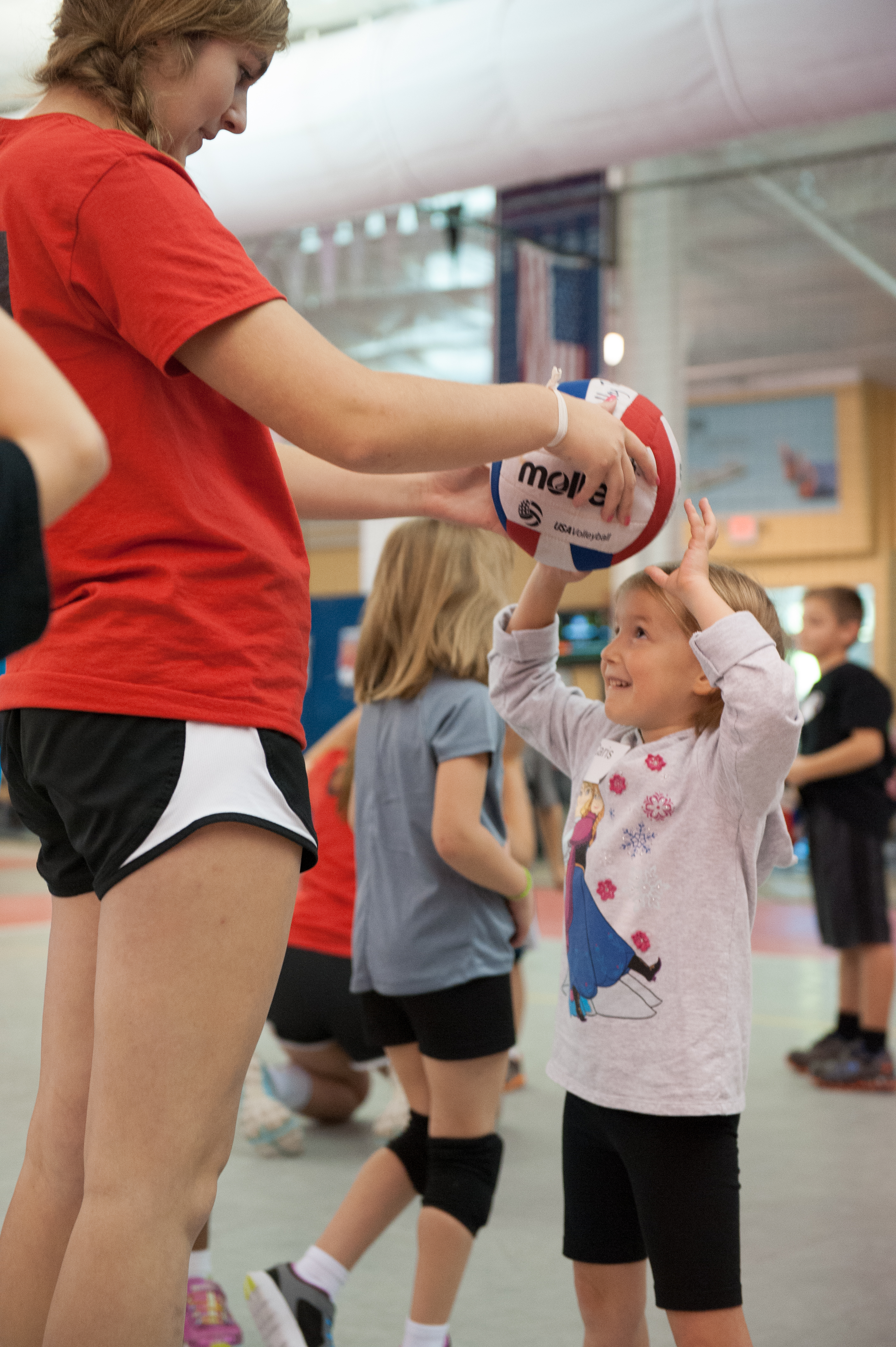 Jumpin Junior player learning to set from coach during kids volleyball practice