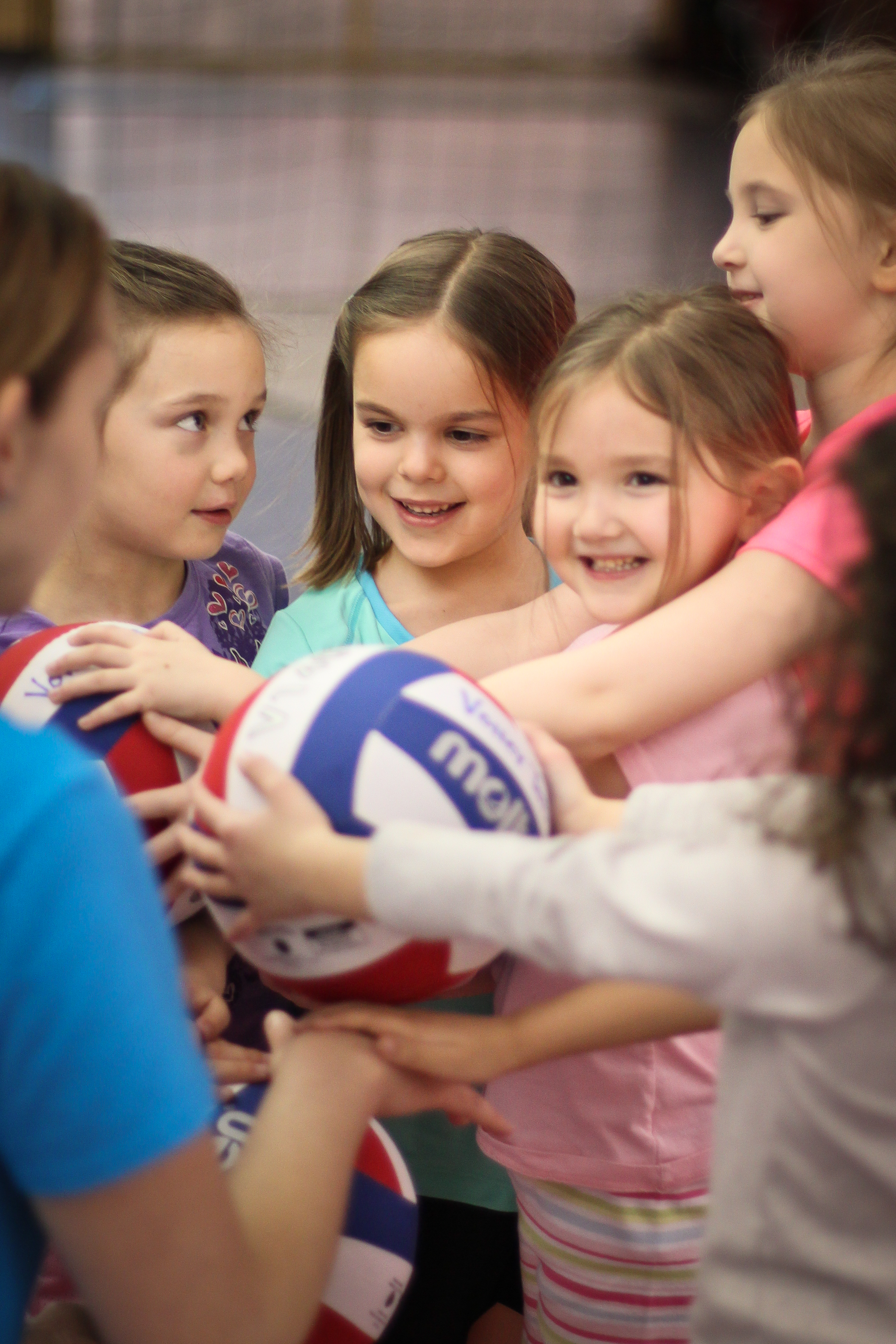 Group of preschoolers holding a  volleyball during Itsy Bitsy Spikers at Richmond Volleyball Club